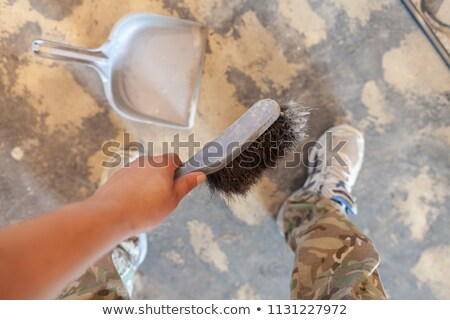 Female hand is sweeping carpet with short handlebroom Stock photo © stevanovicigor