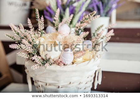 Wicker basket with Easter eggs, flowers and bunny stock photo © orensila