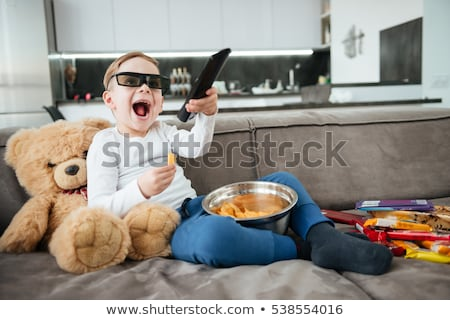 Boy wearing 3d glasses watching TV while eating chips. Stock photo © deandrobot