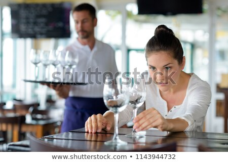 beautiful waitress cleaning wine glass with napkin stock photo © wavebreak_media