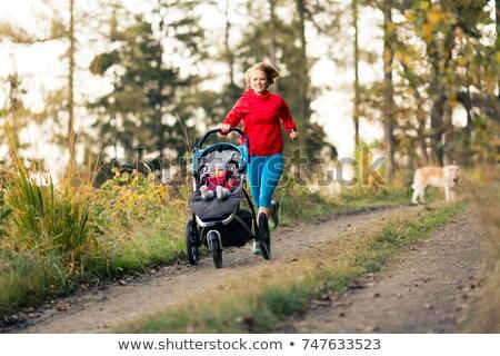 Running mother with stroller enjoying motherhood at autumn sunse Stock photo © blasbike