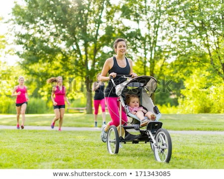 woman exercising with her baby girl in the park stock photo © dashapetrenko