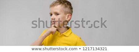 Portrait of cute little blonde caucasian boy in yellow t-shirt unsure puzzled on gray background Stock photo © Traimak