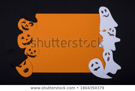 Scary frame from paper handcraft paper pumpkins and ghosts on an orange background with copy space.  Stock photo © artjazz