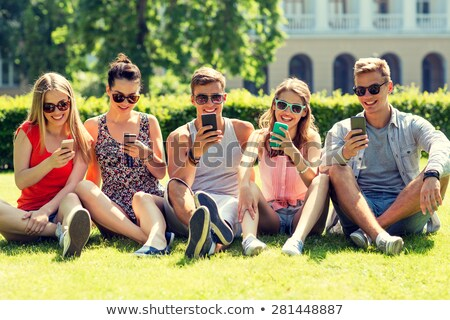 smiling friends with smartphones sitting on grass stock photo © dolgachov