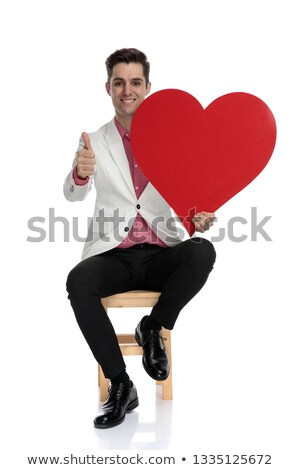 positive young elegant man makes ok sign while holding heart stock photo © feedough