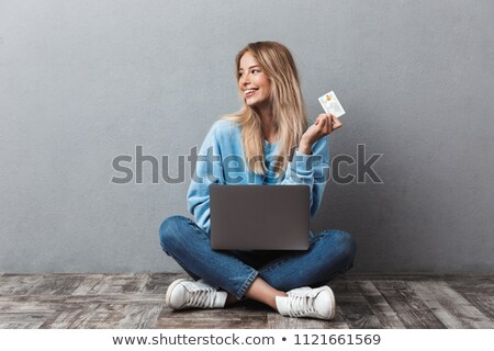 Woman sitting isolated over grey background using laptop computer holding credit card. Stock photo © deandrobot
