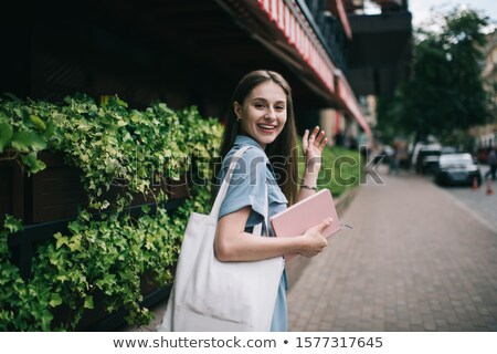 students with notebook waving hands outdoors Stock photo © dolgachov
