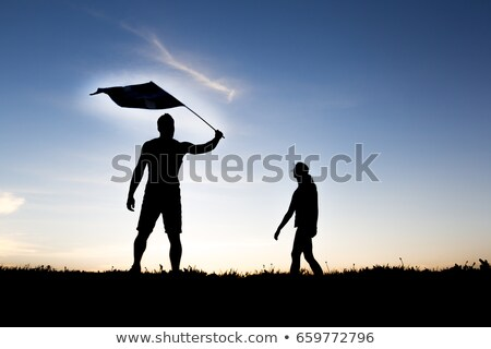 silhouette of two people at with sunset on the back with flag Stock photo © Lopolo