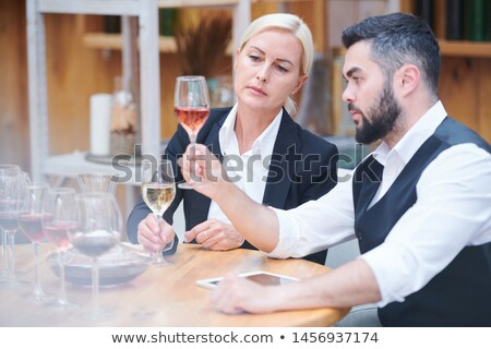 Serious and attentive sommeliers evaluating color of wine sample Stock photo © pressmaster