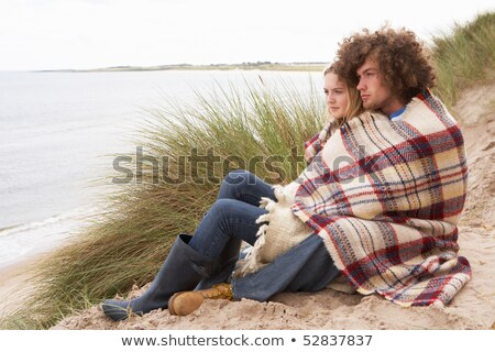 Teenage Couple Sitting In Sand Dunes Wrapped In Blanket stock photo © monkey_business