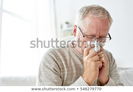sick senior man with paper wipe blowing his nose Stock photo © dolgachov