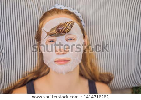 Young woman makes a face mask with snail mucus. Snail crawling on a face mask Stock photo © galitskaya