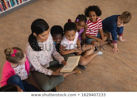 High angle view of female teacher teaching schoolkids and sitting on floor of school library Stock photo © wavebreak_media