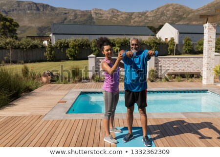 Front view of a female African American trainer assisting senior man in performing exercise next to  Stock photo © wavebreak_media