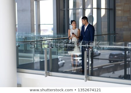 Front view of elegant young mixed-race business people interacting with each other standing in moder Stock photo © wavebreak_media