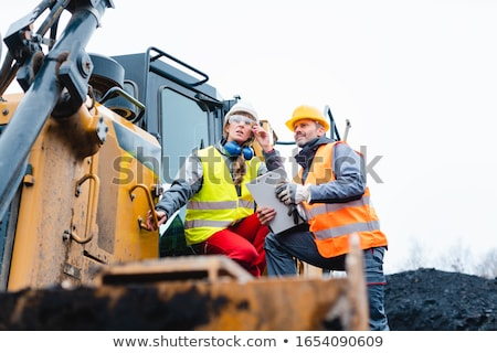 Woman and man worker in quarry on excavation machine Stock photo © Kzenon