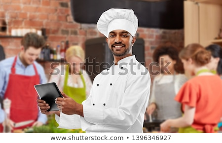 male indian chef with tablet pc at cooking class Stock photo © dolgachov