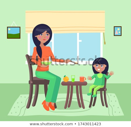 Mother feeding her daughter with a spoon with poridge, little girl having fun or rejoice, smiling Stock photo © robuart