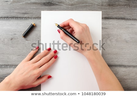 Hand holding a pen and sheet of a paper laying on a desk Stock photo © Pruser