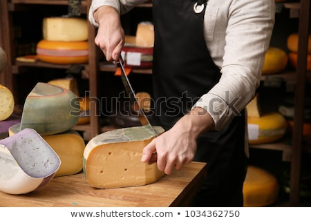 Male hands cutting dutch cheese Stock photo © macsim