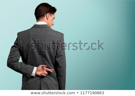 liar businessman with crossed fingers at back isolated on white stock photo © dacasdo