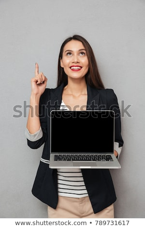 Woman Holding Laptop While Pointing At Copyspace stock photo © Maridav