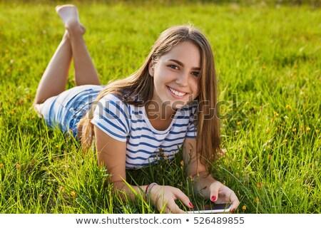Teenage girl lying on grass with phone Stock photo © monkey_business