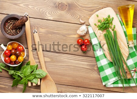 Onions, garlic and spring onions on wooden kitchen cutting board Stock photo © MartinsK
