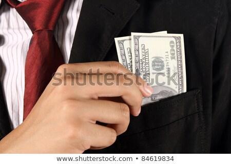 Businessman putting dollar banknotes money in his suit pocket Stock photo © stevanovicigor