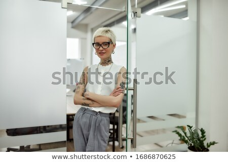 Happy tattooed young woman standing with arms crossed Stock photo © deandrobot