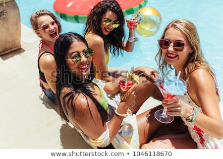 four girls having fun and drinking cocktails at swimming pool stock photo © deandrobot