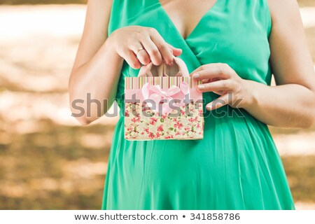 Stock photo: Pregnant woman in green dress pulls out a pink baby booties from