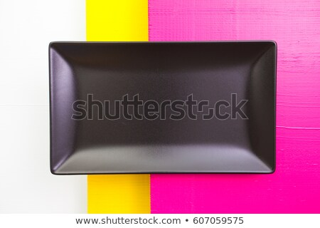 Empty black ceramic dish on over white, yellow and pink   wooden Stock photo © CaptureLight