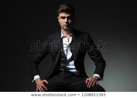 smiling elegant man in tuxedo and undone bowtie sitting Stock photo © feedough