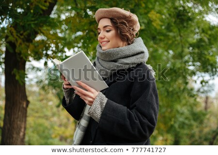 Portrait of a cheery girl dressed in autumn clothes reading Stock photo © deandrobot