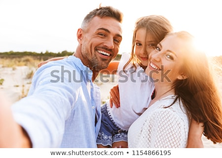 Cheerful family spending good time at the beach Stock photo © deandrobot