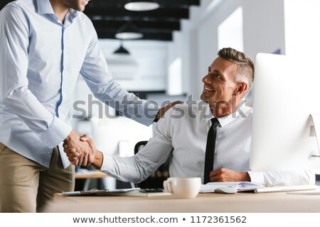 Image of happy businessmen coworkers 30s in formal clothes worki Stock photo © deandrobot