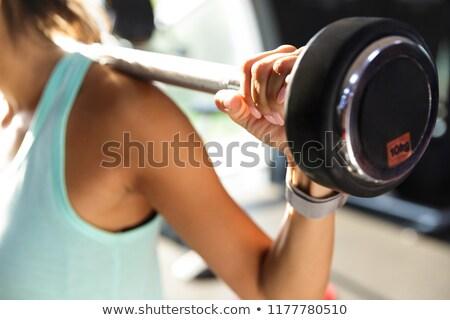Afbeelding verbazingwekkend sport vrouw oefening barbell Stockfoto © deandrobot