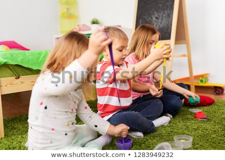 sisters with modelling clay or slimes at home Stock photo © dolgachov