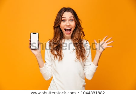 Portrait of shocked woman 20s with long hair surprising and hold Stock photo © deandrobot