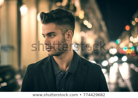 Attractive young man portrait at night with city lights behind him in Turin, Italy Stock photo © Lopolo