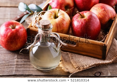 Bottle and glass of homemade organic apple cider with fresh apples in box on wooden background with  Stock photo © DenisMArt