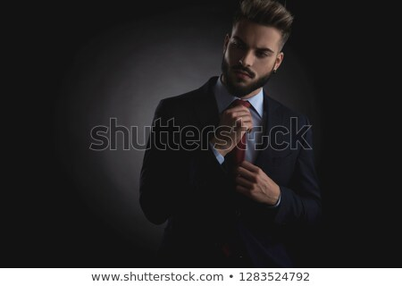 portrait of businessman looking down to side and fixing tie Stock photo © feedough