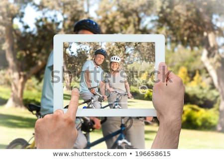 couple with tablet pc and bicycles at summer park stock photo © dolgachov