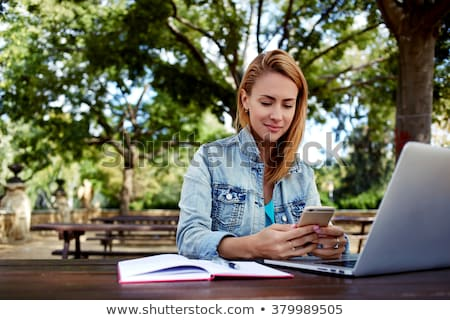 Beautiful young woman using laptop computer outdoors while reading book. Stock photo © deandrobot