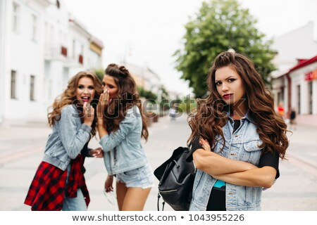 Two girlfriends gossiping about third in the street. Stock photo © studiolucky
