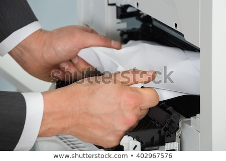 Businessman Removing Stuck Paper In The Printer Stock photo © AndreyPopov