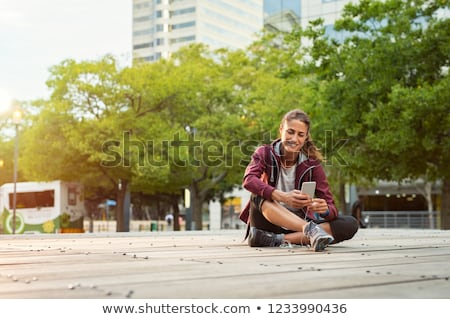 Sports woman in park outdoors listening music with earphones using mobile phone. Stock photo © deandrobot