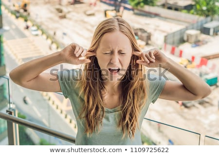 Photo stock: A young woman by the window annoyed by the building works outside. Noise concept